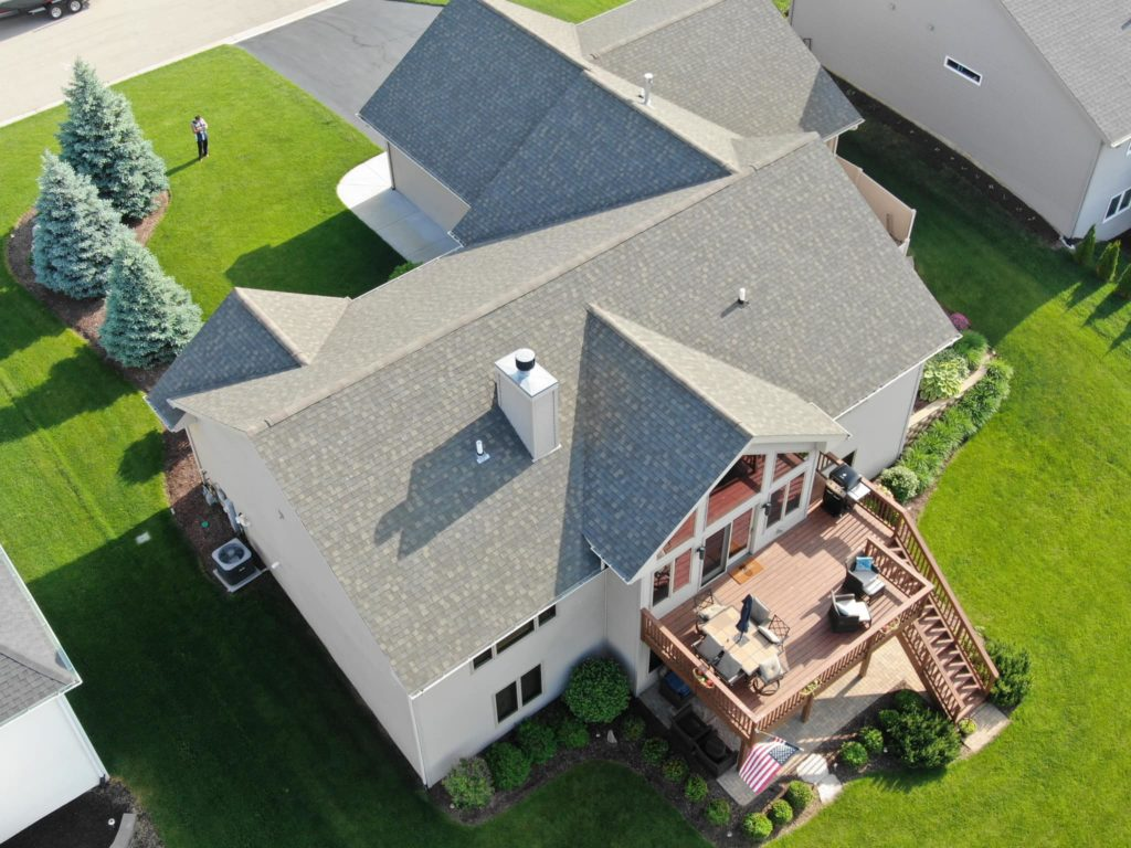 Aerial view of a beautiful residential home with a roof by Pro Restoration LLC